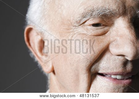 Extreme closeup of a smiling senior man against gray background
