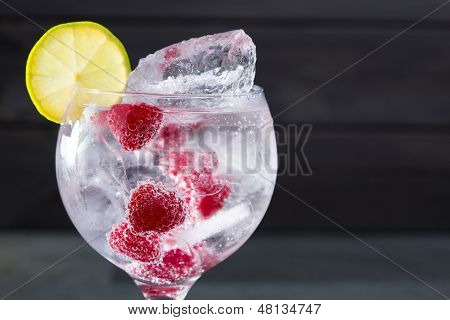 Gin tonic cocktail with raspberry lima slice and ice macro closeup on black