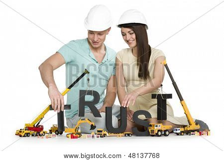 Building up trust concept: Happy young man and woman along with construction machines establishing the word trust, isolated on white background.