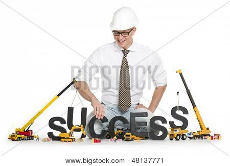 Working on success concept: Smiling businessman working on his success along with construction machines, isolated on white background.