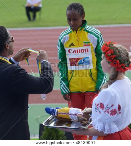 DONETSK, UKRAINE - JULY 11: IAAF Ambassador Ato Boldon hand over silver medal for 3000 m race to Berhan Demiesa, Ethiopia during 8th IAAF World Youth Championships in Donetsk, Ukraine on July 11, 2013
