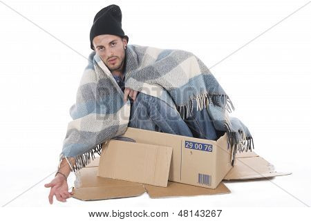 Homeless Man Sitting In His Cardboard Begging