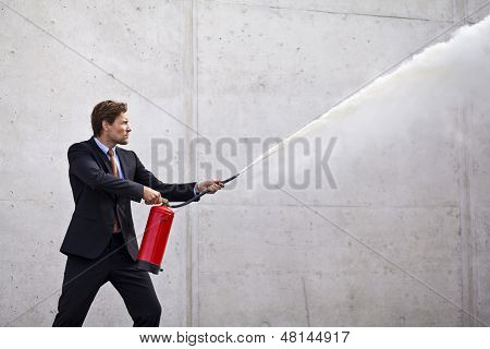 Focused businessman using a fire extinguisher