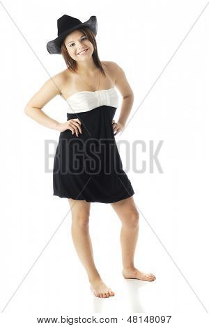 A beautiful barefoot teen looking cocky her strapless dress and a black cowboy hat. On a white background.