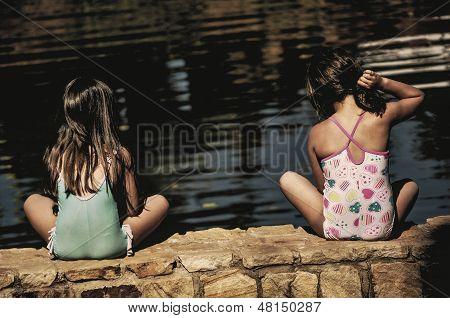 Girls sitting by a pond