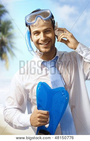 Happy businessman with scuba-diving equipments enjoying summer holiday, pretending to talking on mobile phone.