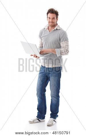 Casual young man holding laptop in hands, smiling.