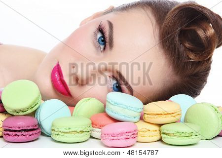 Portrait of young beautiful woman with colorful macaroons