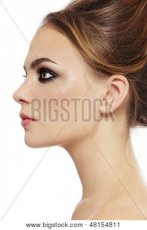 Profile portrait of young beautiful stylish woman with smoky eyes over white background