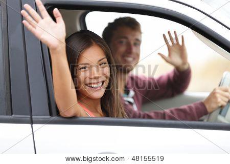 Motoristas dirigindo no carro acenando feliz na câmera. Jovem casal em viagem no carro novo. Hap interracial