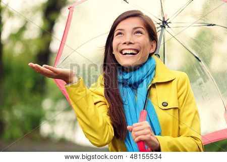 Autumn woman happy after rain walking with umbrella. Female model looking up at clearing sky joyful on rainy fall day wearing yellow raincoat outside in nature forest by lake. Multi-ethnic Asian girl.