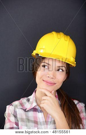 Junge weibliche Architekt, Ingenieur, Landvermesser oder Bau Arbeiter tragen Hardhat denken als sie st