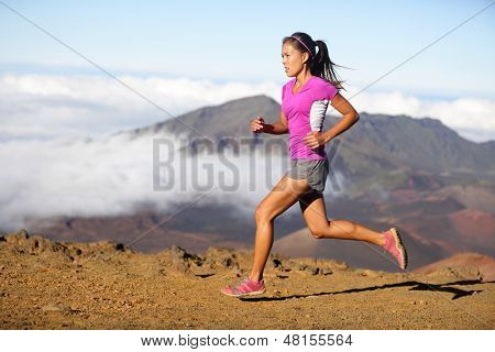 Runner woman athlete running sprinting fast. Female sport fitness model training a sprint in amazing nature landscape outdoors at speed wearing sporty runners clothing outfit. Mixed race Asian woman