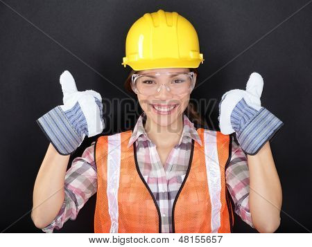 Construction worker happy woman doing thumbs up with protection wear. Young woman wearing safety glasses, vest and yellow hard hat for security and protection on black background. Asian female model.
