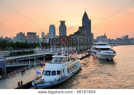 Boat in Huangpu River with Shanghai urban architecture at sunset in dock