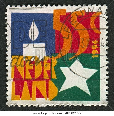 NETHERLAND - CIRCA 1937: A stamp printed in Netherland shows image of the Candle and Star, circa 1937.