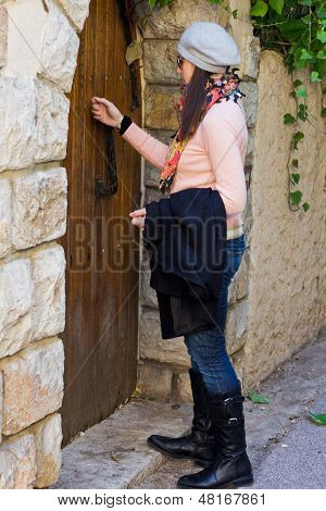 Women Knocking On An Old Wooden Door