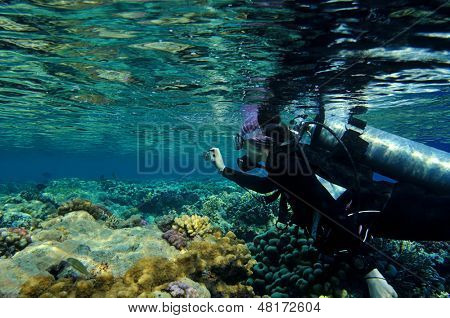 Female diver taking film underwater
