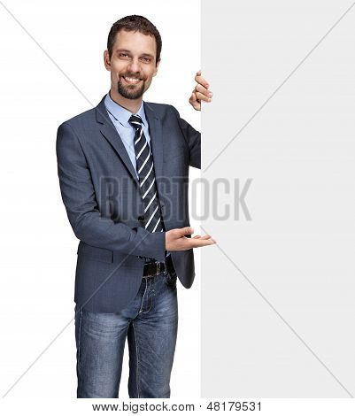 Happy smiling young businessman showing large blank grey signboard isolated on white background