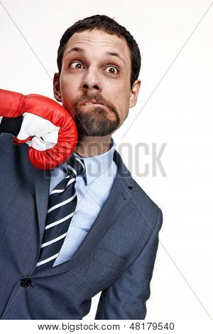 Young business man struck by hand in boxing glove isolated over white background