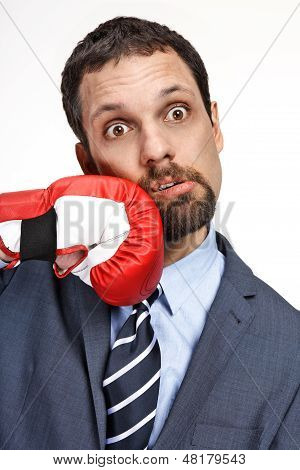 Close-up young business man struck by hand in boxing glove isolated on white background