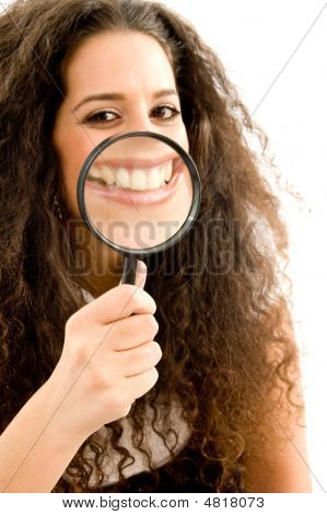 Young Woman Holding Magnifier And Showing Her Magnified Teeth