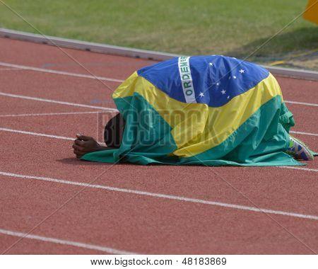 DONETSK, UKRAINE - JULY 14: Silver medalist in 200 metres Vitor Hugo dos Santos of Brazil under national flag during 8th IAAF World Youth Championships in Donetsk, Ukraine on July 14, 2013