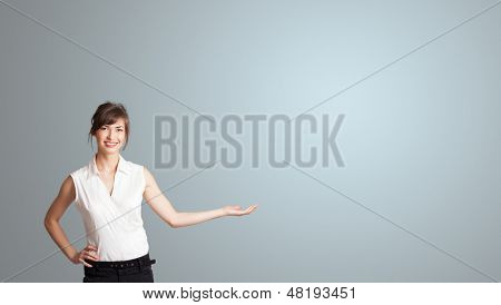 Pretty young woman presenting copy space