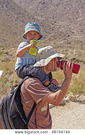 Father And Son Drinking Water While Hiking
