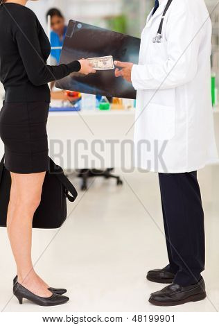 medical rep bribing doctor, hiding money behind x-ray