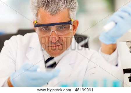 middle aged medical researcher doing microbiology experiment