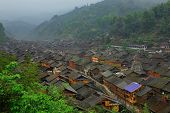 Large village in morning mist, China, mountainous terrain. Zhaoxing Village, Liping County, Guizhou.