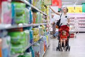 stock photo of diaper  - Mother with her boy in baby carriage in the supermarket - JPG