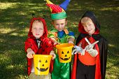 stock photo of greed  - Three boys in Halloween costumes are waiting for their candies - JPG