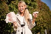 stock photo of early 20s  - Happy girl in early autumn park with candy - JPG