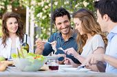 stock photo of spring break  - Group Of Happy Young Friends Having Dinner At Patio - JPG