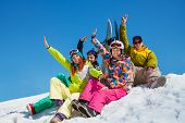 stock photo of snowboarding  - Happy friends men and women sit in snow with snowboards lifting and waving hands - JPG