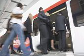 stock photo of commutator  - Low angle view of business commuters getting into a train - JPG