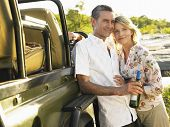 Smiling adult couple standing by jeep with a bottle of wine