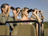 stock photo of  jeep  - Group of happy tourists sitting in jeep and looking through binoculars - JPG
