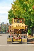 stock photo of oversize load  - Lowboy moving a large Bulldozerr from a construction site in Roseburg Oregon - JPG