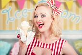 stock photo of pinup girl  - Attractive retro pinup girl eating ice cream cone inside a vintage ice creamery - JPG