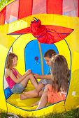 Three kids playing inside the camping tent