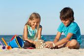 stock photo of conch  - Kids playing on the beach building a sand castle decorating it with seashells - JPG