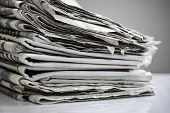 Daily newspapers stacked in a heap