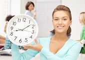 education and time management - attractive student pointing at clock
