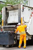 stock photo of trash truck  - Worker of municipal recycling garbage collector truck loading waste and trash bin - JPG