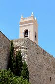 image of senora  - Torreon de la Pezza ancient fortified wall and the tower bell of parish church Nuestra Senora de las Nieves located in the Calp old town - JPG