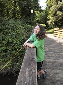 stock photo of brook trout  - Vertical photo of young girl looking forward fishing off of wooden bridge for trout with stream walk path and trees in background - JPG