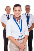 attractive airhostess standing in front of pilots on white background